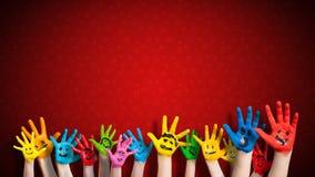 Mani dipinte dei bambini con lo smiley davanti al fondo di natale fotografie stock