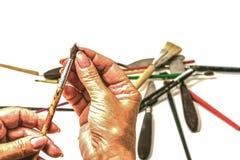 Mani dorate dell'artista che sceglie una spazzola immagine stock libera da diritti