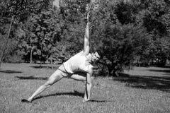 Mani e gambe di allungamento dell'atleta sulla stuoia blu in parco Fotografia Stock