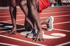 Mani e piedi di un uomo dalla carnagione scura sulla pista dello stadio Fotografie Stock Libere da Diritti