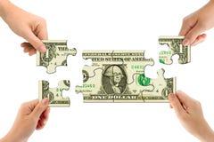 Mani e puzzle dei soldi Fotografia Stock