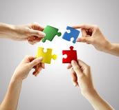 Mani e puzzle su priorità bassa grigia Immagini Stock Libere da Diritti