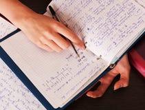 Mani e taccuino dell'allievo con la penna Fotografie Stock