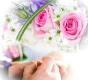 Mani ed anelli sul mazzo di cerimonia nuziale Immagine Stock