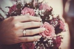 Mani ed anelli sul mazzo di cerimonia nuziale Fotografie Stock