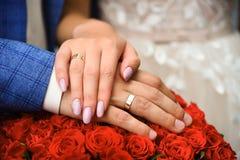 Mani ed anelli sul mazzo di nozze delle rose rosse immagine stock libera da diritti