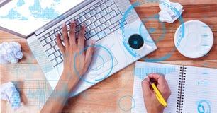 Mani facendo uso del computer portatile e della scrittura allo scrittorio con la sovrapposizione Immagini Stock Libere da Diritti