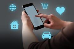 Mani facendo uso del telefono cellulare con le icone blu-chiaro illuminate Immagine Stock