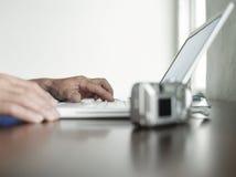 Mani facendo uso dell'ufficio del computer portatile a casa fotografie stock libere da diritti
