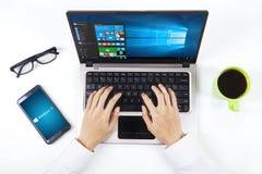 Mani facendo uso delle finestre 10 sul computer portatile e sullo smartphone Fotografie Stock