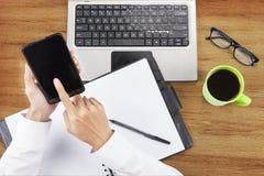 Mani facendo uso dello smartphone da lavorare Immagine Stock Libera da Diritti