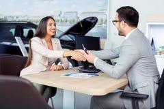 Mani felici di scossa del commerciante e del cliente di automobile dopo il contratto con successo firmato immagine stock libera da diritti
