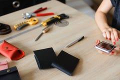 Mani femminili all'atelier di cuoio facendo uso dello smartphone, dei portafogli fatti a mano e degli strumenti sulla tavola Immagine Stock