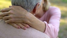 Mani femminili che abbracciano il collo del marito, vecchia coppia che bacia e che abbraccia, amore maturo fotografia stock