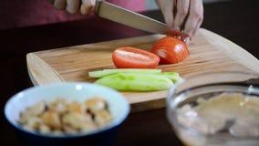 Mani femminili che affettano pomodoro rosso, colpo del carrello stock footage