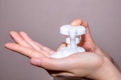 Mani femminili che applicano sapone liquido fotografia stock libera da diritti