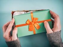 Mani femminili che aprono il contenitore di regalo Fotografia Stock