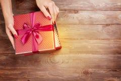 Mani femminili che aprono il regalo di natale Immagini Stock