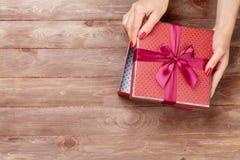 Mani femminili che aprono il regalo di natale Fotografie Stock