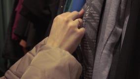 Mani femminili che cercano vestito al deposito dei vestiti video d archivio