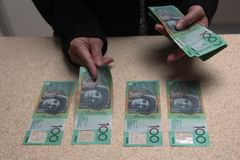 Mani femminili che contano australiano 100 dollari di fatture Immagine Stock Libera da Diritti