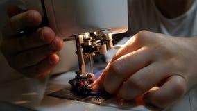 Mani femminili che cucono su una macchina per cucire moderna archivi video
