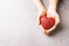 Mani femminili che danno cuore rosso Fotografia Stock Libera da Diritti