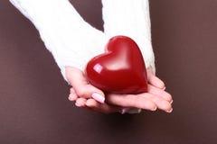 Mani femminili che danno cuore rosso, isolato sul fondo dell'oro Immagine Stock Libera da Diritti