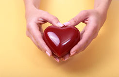 Mani femminili che danno cuore rosso, isolato sul fondo dell'oro Fotografie Stock Libere da Diritti
