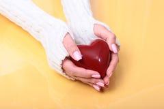 Mani femminili che danno cuore rosso, isolato sul fondo dell'oro, amore di inverno di natale Fotografia Stock