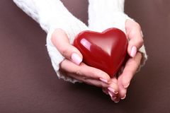 Mani femminili che danno cuore rosso, isolato sul fondo dell'oro, amore di inverno di natale Immagini Stock