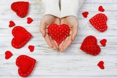Mani femminili che danno cuore rosso Priorità bassa di giorno del biglietto di S Fotografia Stock