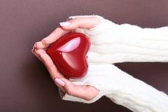 Mani femminili che danno cuore rosso, sul fondo dell'oro, amore di inverno di natale Fotografia Stock Libera da Diritti