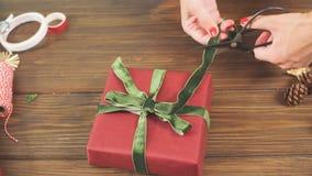 Mani femminili che decorano i contenitori rossi di regalo per la festa di Natale Le mani si chiudono in su archivi video