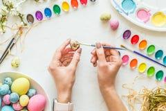 Mani femminili che dipingono le uova di Pasqua Concetto di festa Disposizione piana Vista superiore fotografia stock libera da diritti