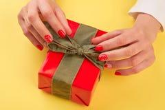 Mani femminili che disimballano il contenitore di regalo rosso Fotografia Stock Libera da Diritti