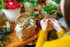 Mani femminili che fanno bello mazzo dei fiori sul fondo fotografia stock libera da diritti