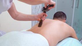Mani femminili che fanno massaggio del Sen del tok con il martello tailandese sulla parte posteriore del paziente maschio stock footage