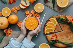 Mani femminili che giudicano frullato arancio decorato con alstroemeria con la torta arancio Fotografia Stock Libera da Diritti
