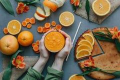 Mani femminili che giudicano frullato arancio decorato con alstroemeria con la torta arancio Immagini Stock Libere da Diritti