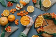Mani femminili che giudicano frullato arancio decorato con alstroemeria con la torta arancio Fotografie Stock