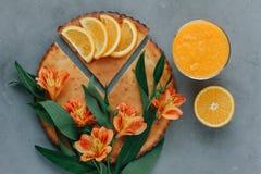 Mani femminili che giudicano frullato arancio decorato con alstroemeria con la torta arancio Immagine Stock