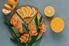 Mani femminili che giudicano frullato arancio decorato con alstroemeria con la torta arancio Fotografia Stock