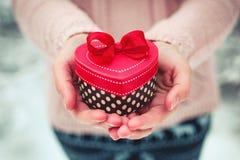Mani femminili che giudicano un regalo a forma di scatola di cuore Il giorno e la cartolina di Natale di biglietti di S. Valentin Immagine Stock