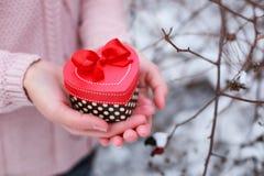 Mani femminili che giudicano un regalo a forma di scatola di cuore Il giorno e la cartolina di Natale di biglietti di S. Valentin Immagini Stock
