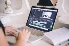 Mani femminili che lavorano ad un computer portatile in un video programma di editing fotografia stock