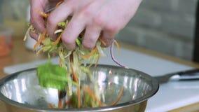 Mani femminili che mescolano insalata di verdure in ciotola lentamente video d archivio