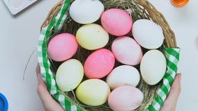 Mani femminili che mettono canestro con le uova di Pasqua variopinte sulla tavola, preparazione del fest video d archivio