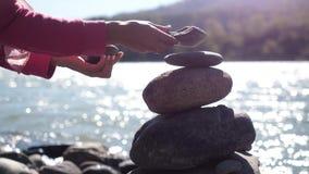Mani femminili che mettono la pila del ciottolo accanto al fiume della montagna il giorno soleggiato con gli effetti del chiarore fotografie stock