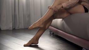 Mani femminili che mettono sulle calzamaglia di nylon nella camera da letto, preparantesi per il partito di notte immagini stock